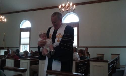 Infant being baptized by sprinkling at the Paoli United Methodist Church.